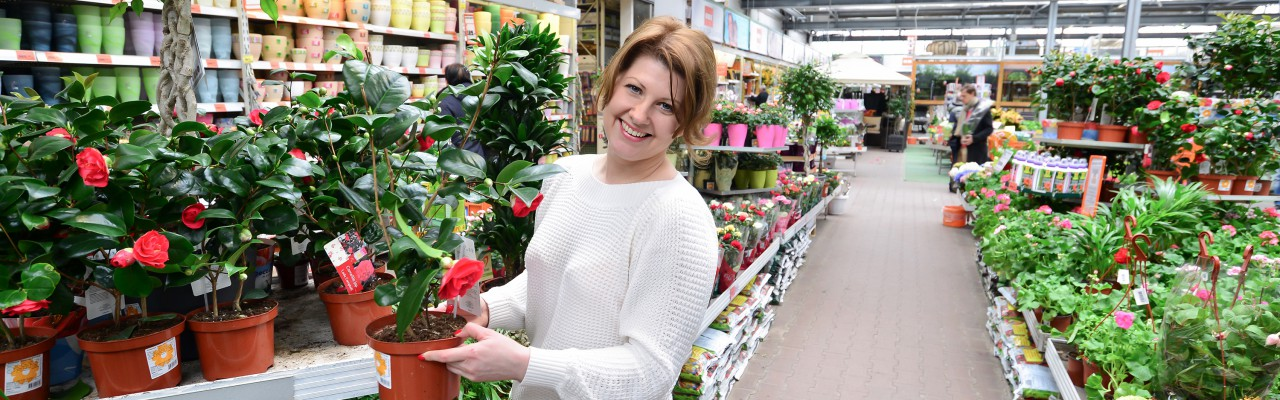 woman holding flowers working in a garden centre